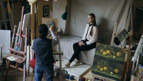 Скульптор создавая скульптуру человеческой стороны ` s на холсте пока молодая женщина представляя к нему в студии искусства Стоковое фото RF