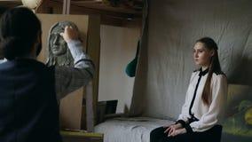 Скульптор создавая скульптуру человеческой стороны ` s на холсте пока молодая женщина представляя к нему в студии искусства Стоковые Изображения