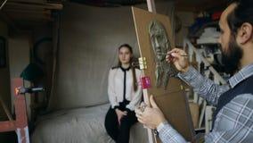 Скульптор создавая скульптуру человеческой стороны ` s на холсте пока молодая женщина представляя его в студии искусства Стоковая Фотография RF
