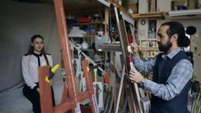 Скульптор создавая скульптуру человеческой стороны ` s на холсте пока молодая женщина представляя его в студии искусства Стоковые Фотографии RF