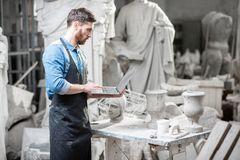 Скульптор с ноутбуком в студии стоковые изображения rf