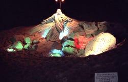 Скульптура песка Иисуса осветила вверх вечером стоковые изображения