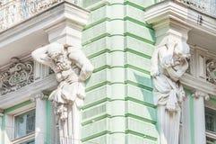 Скульптуры Atlantes на фасаде здания на улице Ilinka стоковые изображения