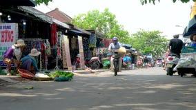 Скутеры, держатели стойла и люди на улицах дневного времени на Hoi рынок, Вьетнам сток-видео