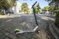 Скутеры пинком Dockless электрические от скутер-деля системы припаркованной на тротуаре стоковые фото
