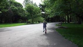 Скутер катания ребенка в девушке парка ослабляя на открытом воздухе делая детей спорта в природе 4K акции видеоматериалы