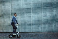 Скутер катания человека перед современным фасадом стоковые изображения