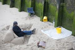 Скульптор создает песок пока прилив вне на южном береге реки Темзы в центральном Лондоне, Великобританию софы стоковые изображения