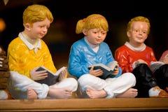 Скульптура детей сидя и читая книга стоковые фотографии rf