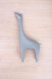 Скульптура жирафа керамическая на деревянной предпосылке Стоковые Изображения RF