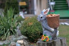 Скульптура зайца нося корзину с конусами ели Стоковые Изображения