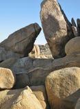 Скульптурные валуны песчаника против голубого неба, формируя триангулярное окно к ландшафту пустыни за пределами Стоковая Фотография