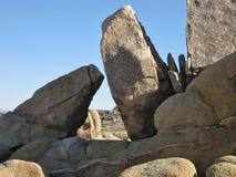 Скульптурные валуны песчаника с видимыми вторжениями расплавленной породы и триангулярное окно к ландшафту пустыни за пределами Стоковые Изображения