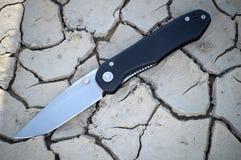Складывая карманный нож с черными лож ручки раскрывает на треснутое сухом Стоковые Фото