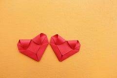 2 складывая красных бумажных сердца на желтой бетонной стене для картины Стоковое Фото