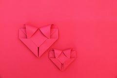 2 складывая красных бумажных сердца на красном цвете для картины и предпосылки Стоковая Фотография