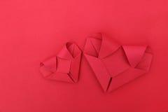 2 складывая красных бумажных сердца на красном цвете для картины и предпосылки Стоковые Изображения