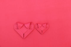 2 складывая красных бумажных сердца на красном цвете для картины и предпосылки Стоковое Фото
