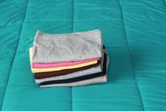 складывая одежды на кровати перед держать Стоковые Фото
