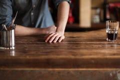 Склонность бармена на деревянном счетчике бара Стоковая Фотография