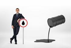 Склонность бизнесмена на дорожном знаке и масло лить из черного бочонка Стоковые Фото