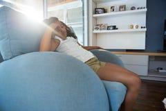 Склонность девушки на кресле Стоковое Изображение RF