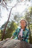 Склонность девушки на утесе в лесе на солнечный день Стоковые Фото