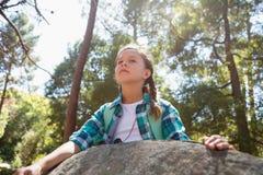 Склонность девушки на утесе в лесе Стоковое фото RF