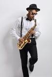 Склонность джазового музыканта против стены и саксофона играть Стоковая Фотография