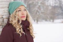 Склонность женщины против дерева в зиме Стоковое Фото