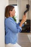 Склонность женщины против стены смотря мобильный телефон дома Стоковая Фотография RF
