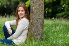 Склонность красивой молодой женщины сидя против дерева Стоковые Фото