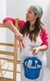 Склонность маленькой девочки на лестнице готовой для того чтобы покрасить стены стоковое изображение rf
