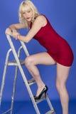 Склонность молодой женщины на лестнице шага нося короткое красное платье Стоковая Фотография RF