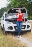 Склонность молодой женщины на сломленном автомобиле и говорить телефоном Стоковое Изображение RF