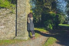 Склонность молодой женщины против каменной стены Стоковое Фото