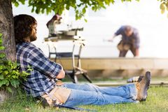 Склонность рабочий-строителя на стволе дерева стоковое фото rf