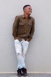 Склонность чернокожего человека полного тела счастливая против серой стены Стоковая Фотография RF