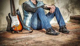 Склонность человека и гитары против стены Стоковые Изображения RF