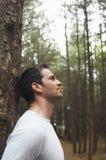 Склонность человека на стволе дерева в лесе Стоковые Фото