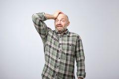 Слабонервный вспугнутый европейский парень имеет sorrorful выражение, держа руки на головном узнает о трагическом событии стоковое фото