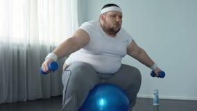 Слабый брюзгливый мужчина борясь для того чтобы поднять гантели, недостаток физической активности, диеты сток-видео