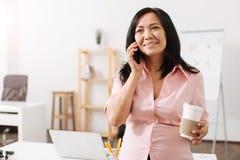Славная беременная женщина говоря на телефоне в офисе Стоковое Изображение