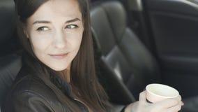 Славная девушка сидит в переднем месте в автомобиле и кофе напитков акции видеоматериалы