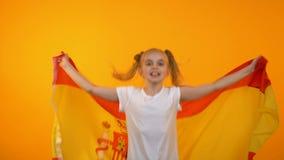 Славная девушка скача с испанским флагом веселя для любимой футбольной команды, вентилятор видеоматериал