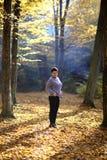 Славная зрелая женщина стоит на предпосылке желтой осени Зрелая женщина леса осени Стоковые Фото
