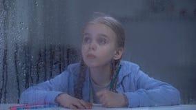 Славная картина маленькой девочки за дождливым окном, сиротским ребенком мечтая о доме видеоматериал