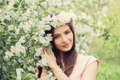 Славная молодая женщина усмехаясь и держа цветки Стоковое Изображение