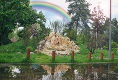 Славная радуга лета над montains радуга, скалистая гора горы отражены в воде Большие желтые камни стоковые фото