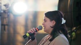 Славная смотря женщина брюнета нося бежевое пальто говорит на микрофоне на этапе видеоматериал